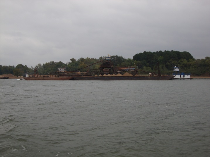 Dredging operation mid river.  It looks like they actually separate the sand, gravel and larger rocks onto different barges.