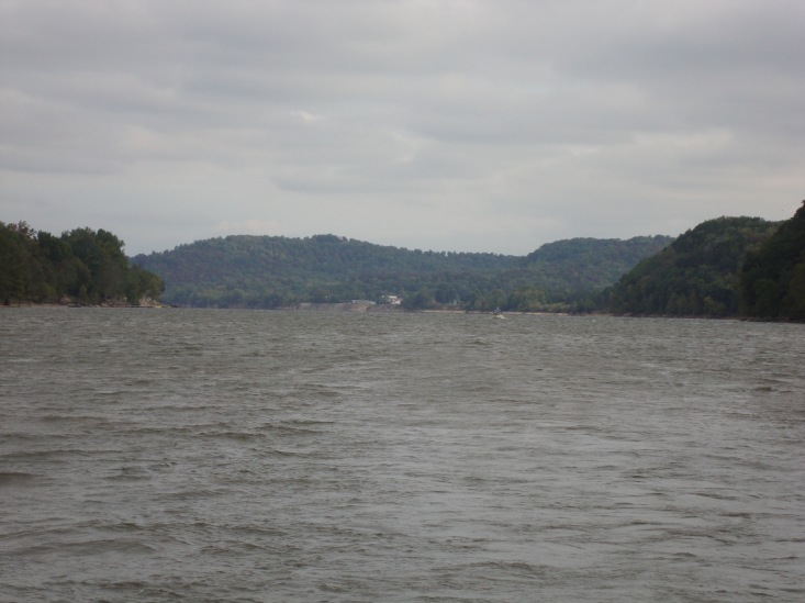 Namaste plugging along upstream on the Tennessee River.  A sailboat without a mast is low on the water.