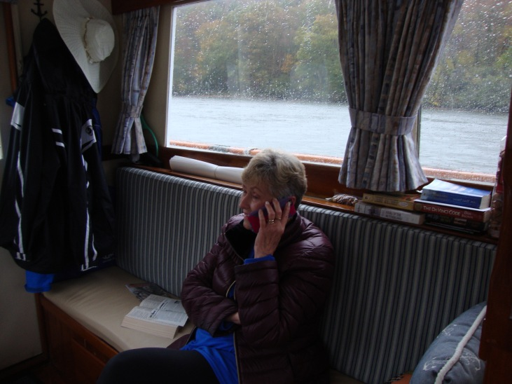 Vicki wiles away the time when there is a cell signal .  It was pouring down rain so the scenery was pretty dismal.